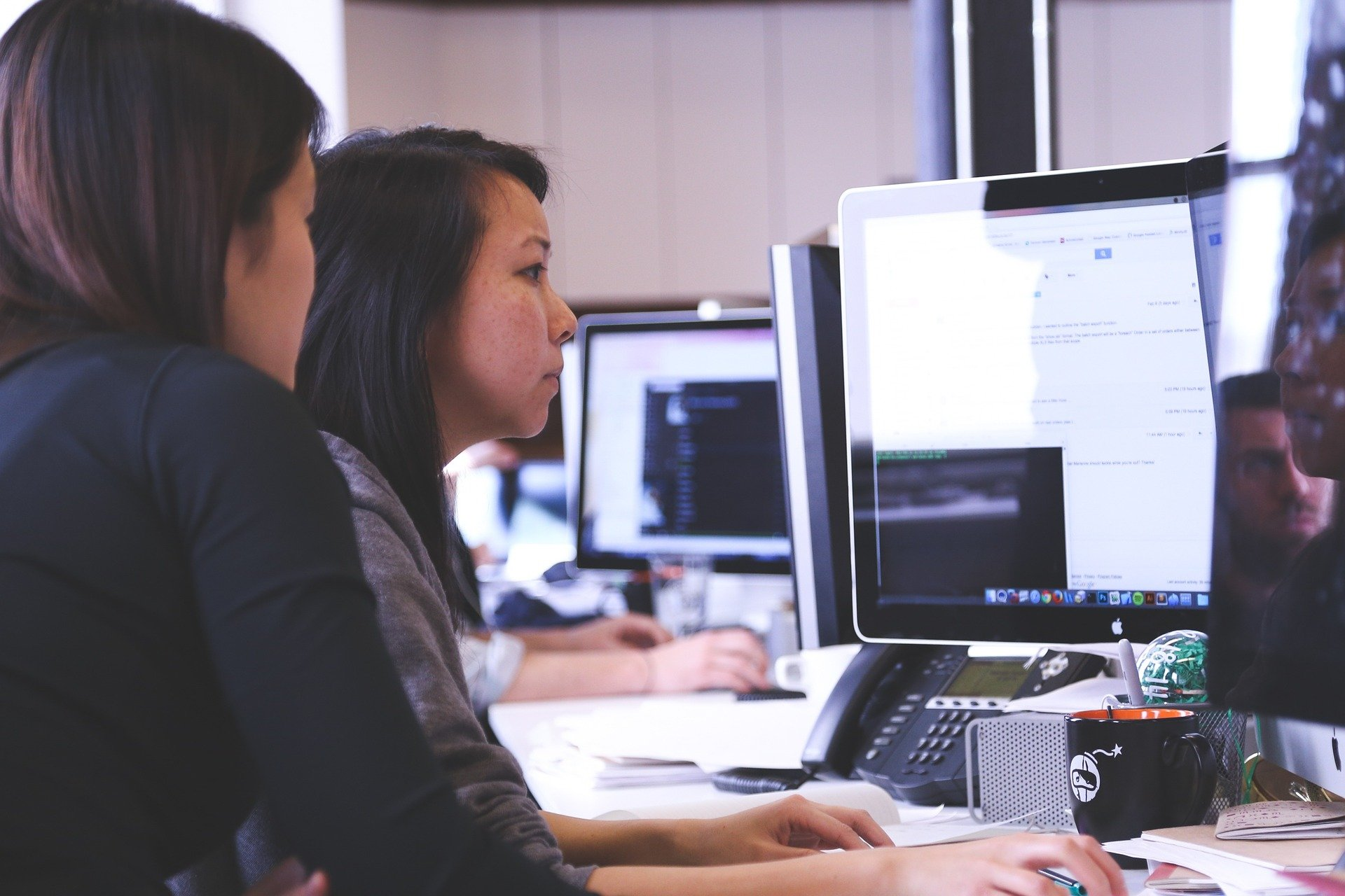 This image shows two women working together in front of a computer